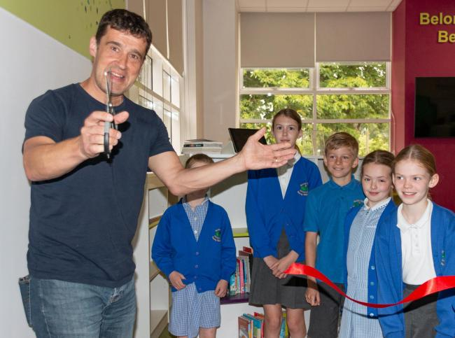 Tom Palmer cuts the ribbon to officially open Burley Oaks Primary School's new library
