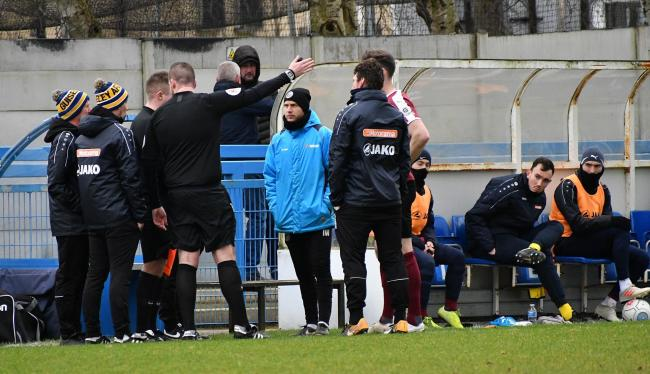 Referee Kristian Silcock talks to Guiseley officials about the racial abuse claims