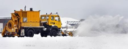 Snow ploughs battle to clear the runway at Leeds Bradford Airport to enable flights to depart.