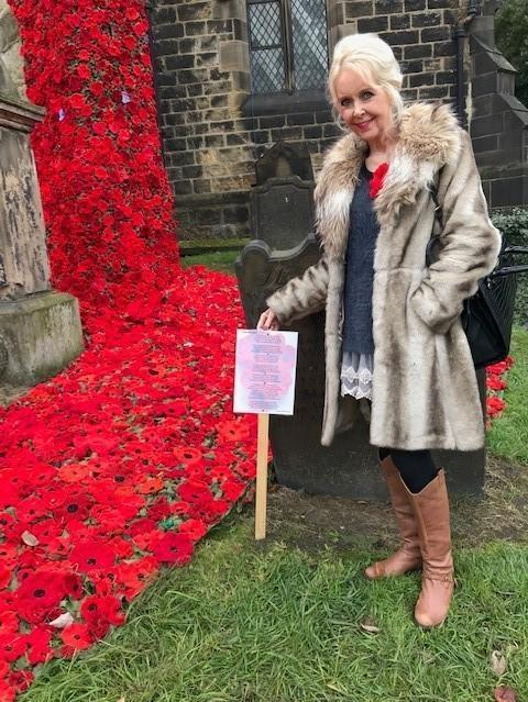 Barbara Corney with one of her poems on display outside Otley Parish Church