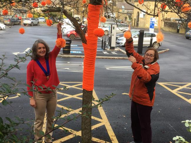 From left: Councillor Ros Brown Deputy Mayor Ilkley Town Council and Jo Thornley President of Ilkley Soroptimists putting the finishing touches to the 'orange tree' in Ilkley's main carpark