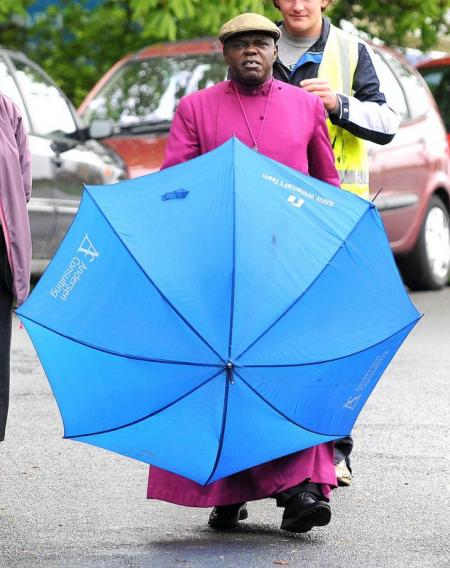 The Archbishop of York gets protection from the rain.
