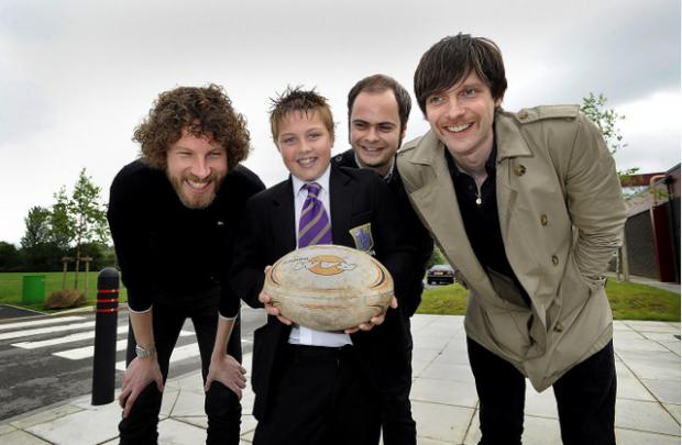 Ilkley Gazette: Simon Rix, Nick 'Peanut' Baines and Nick Hodgson from the Kaiser Chiefs on an earlier visit to St Mary's School in Menston, when they presented a sports award to pupil Josh Inglis.