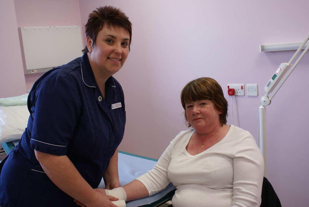 Deborah Jackson demonstrates bandaging a sprained wrist on receptionist Helen Holland, the kind of injury the unit is designed to deal with.