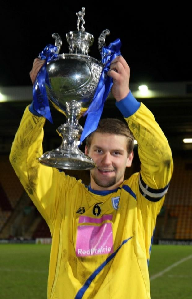 Simon Ainge lifts the trophy