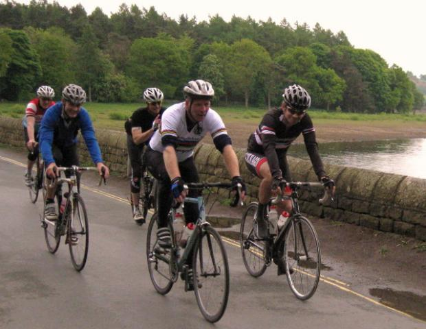 Ilkley Cycling club riders passing over the Swinsty Reservoir dam.