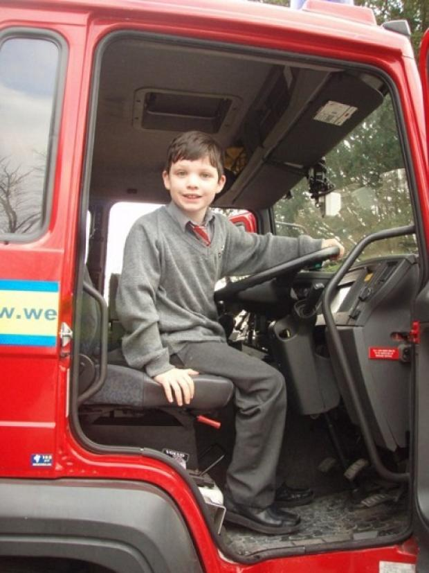 Alex Conway, five, sits in the cab of a fire engine during a visit by firefighters to Ghyll Royd School.