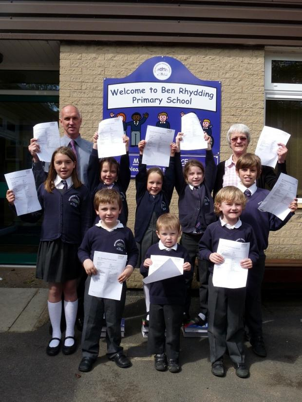 Pupils and teachers at Ben Rhydding Primary School with copies of their good Ofsted report