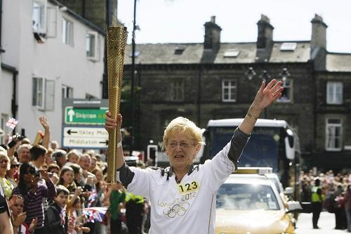 Margaret Cook carries the Olympic flame through Ilkley