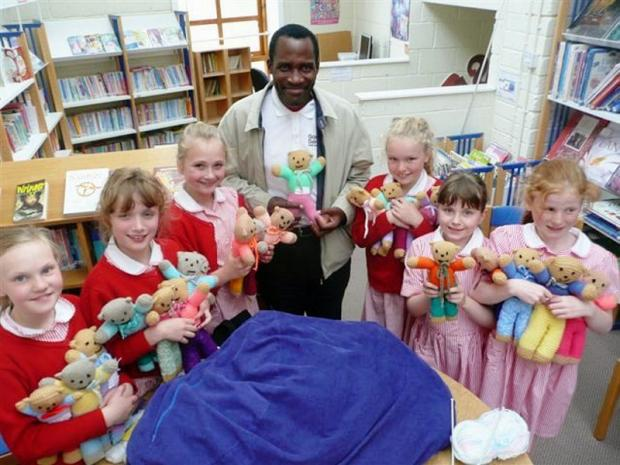 Moorfield School's knitting club present the teddy bears they have made for an African orphanage to Pastor Ivan
