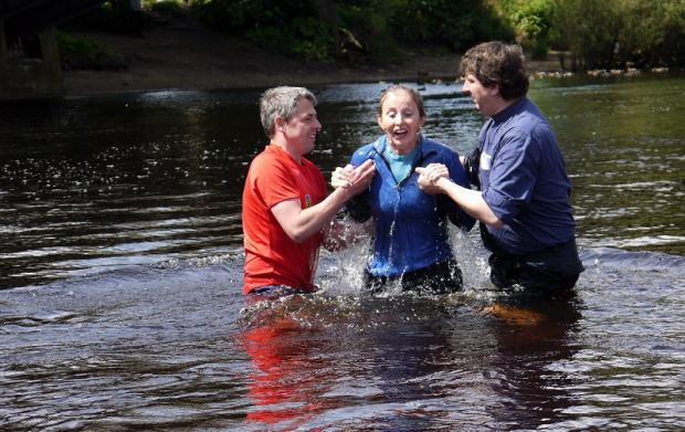 Worshippers take dip in river for baptism service