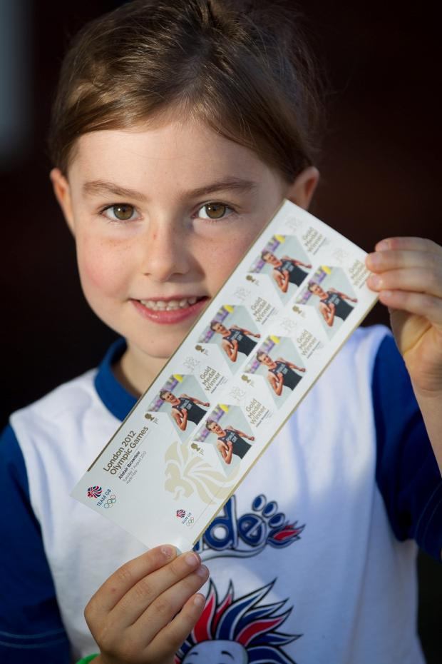 Six-year-old Amelie Stevens, above, poses for a photograph holding specially-made Alistair Brownlee stamps, which went on sale yesterday
