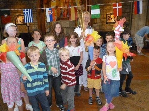 Olympic torchbearer Margaret Cook visits Churches Together in Ilkley's Holiday Club with her gold-coloured torch to talk to children about her special experience