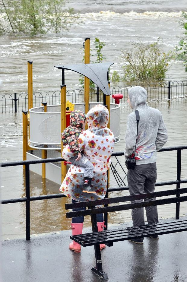 A family survey the flooded children's play area at Wharfemeadows Park in Otley and top the warning sign posted on the gates