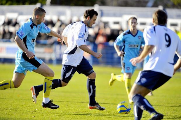 Guiseley'sAndy Holdsworth keeps his eyes on the ball in some heavy traffic