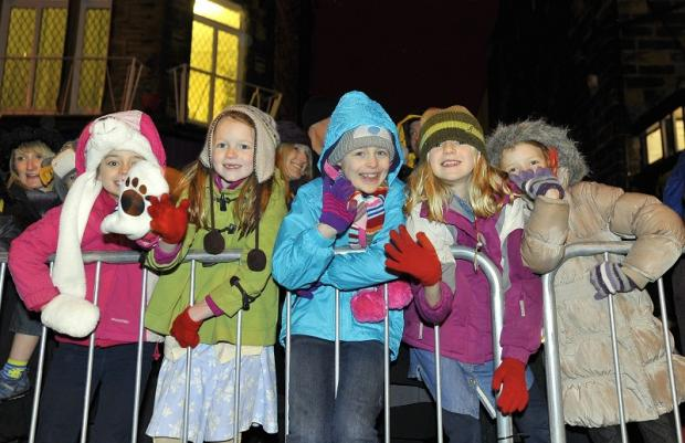 Ilkley Gazette: Well wrapped up, these smiling youngsters were among hundreds who saw the Christmas lights come on in Ilkley. Despite the heavens opening, nothing could stop the fun and excitement at the switch-on.