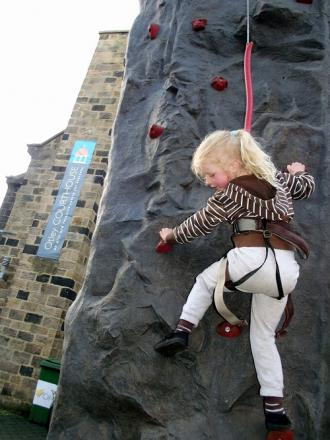 A young girl tries out the climbing wall