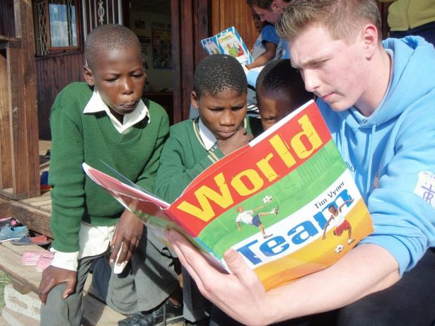Sport plays a large part in the collaboration scheme. Here, a student reads to two children
