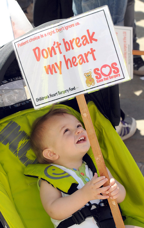 A young boy helps protest against closure of the Leeds children's heart surgery unit in July 2012