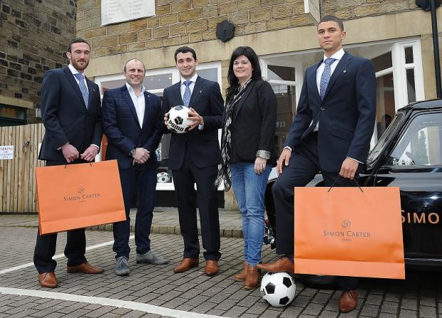 City players Rory McArdle, Carl McHugh and Nahki Wells in their Wembley suits at Simon Carter in Ilkley, with store managers, Julie and Chris Ogden