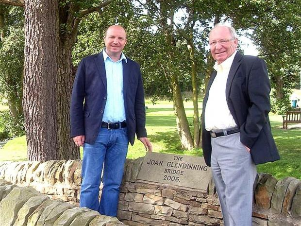 Paul and John Glendinning stand next to a memorial at Otley Golf Club in memory of  Joan Glendinning who died from breast cancer