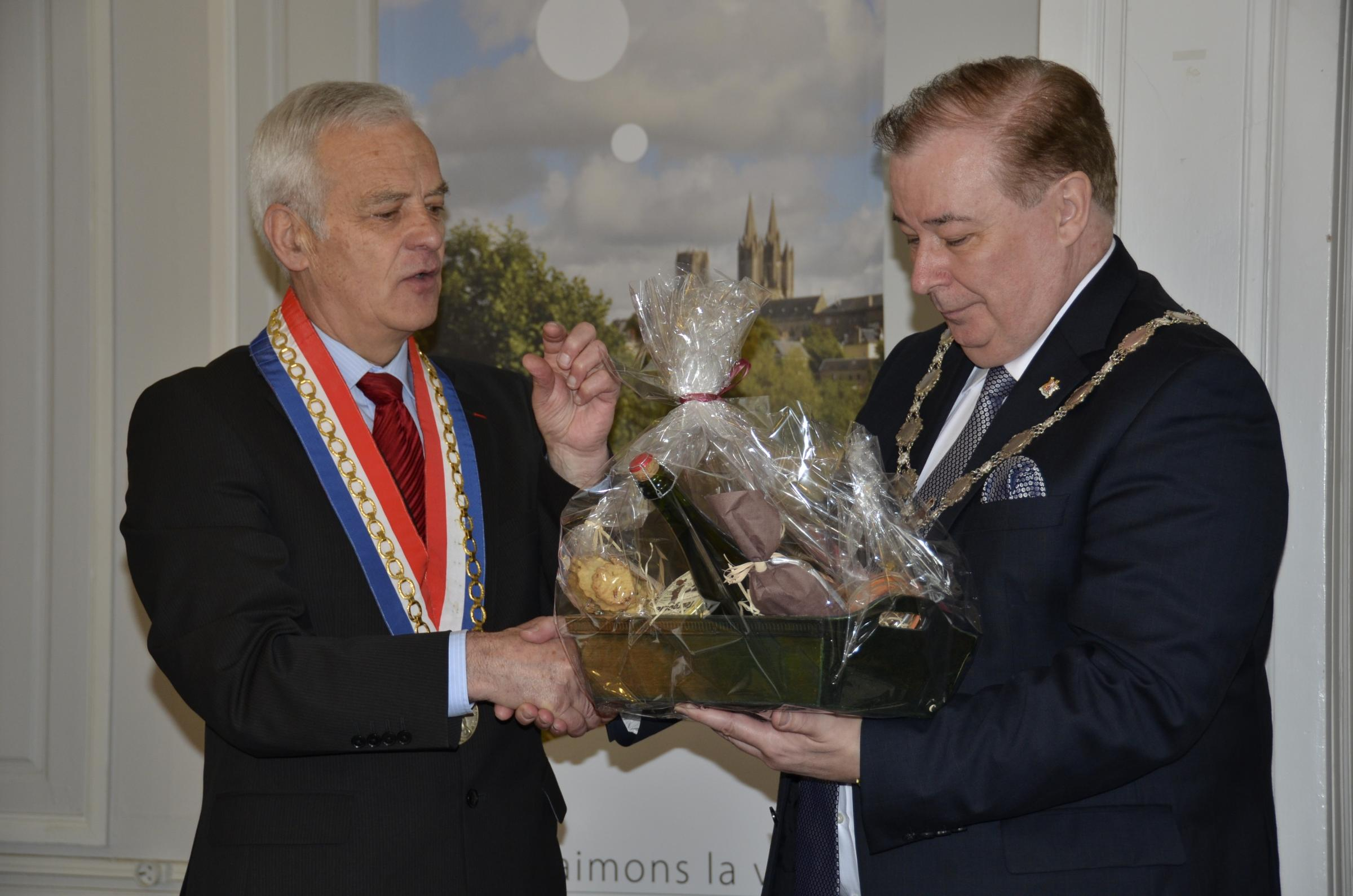 The mayor of Coutances, Monsieur Yves Lamy, presents Coun Mike Gibbons with a basket of deli