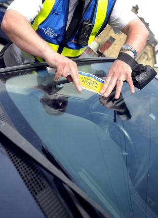 A parking services worker issues a ticket