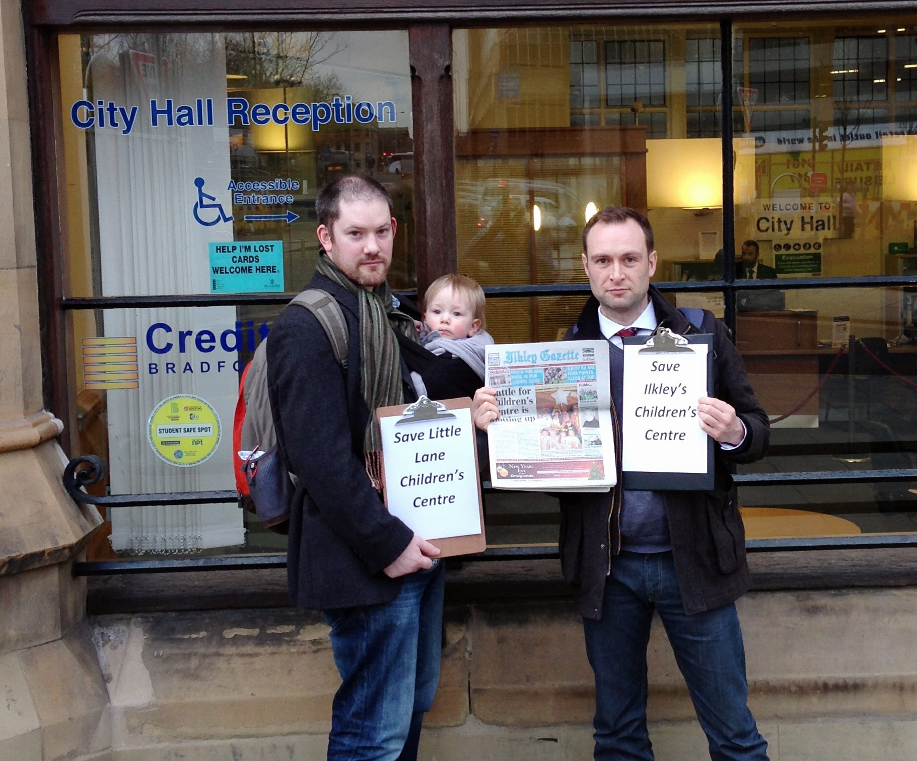 A petition to save Little Lane Children's Centre in Ilkley was presented to a full meeting of Bradford Council. Pictured is Simon Kelly, right, and Adam Lucas who is holding one-year-old Isaac Lucas
