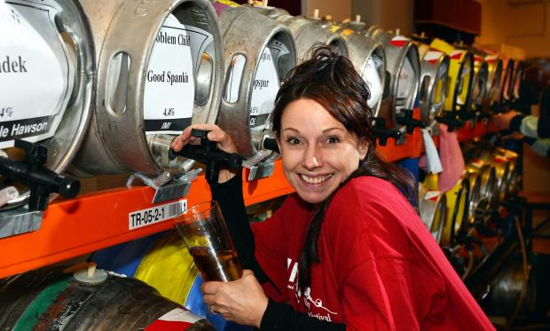 Ilkley Gazette: Sarah-Jane Peters, from Guiseley, helps out at the festival and pours herself a pint