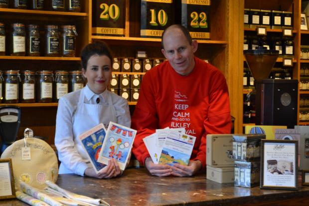 Ilkley Gazette: Bettys retail assistant Chloe Burns and Ilkley Carnival chairman Andrew Stacey, launch the 2014 Ilkley Carnival Cover Competition in Bettys in Ilkley with a look back at the event's programmes from the past decade