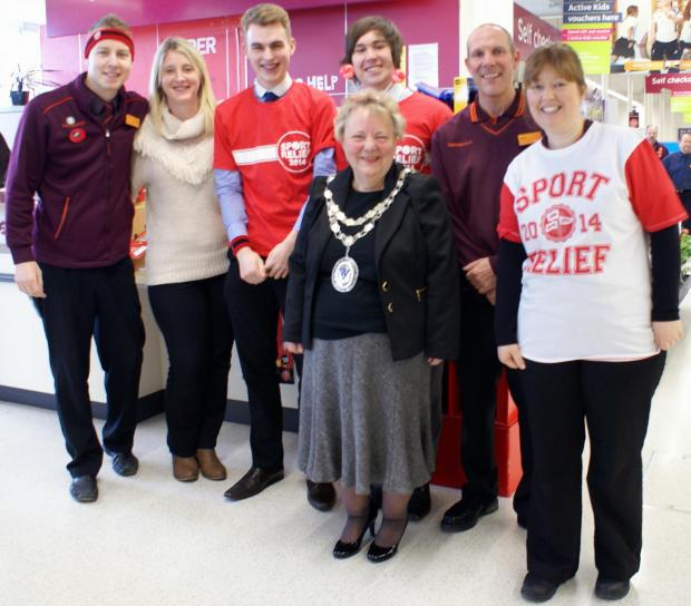 Ilkley Gazette: Otley Town Mayor Pam Gill, centre, with Prince Henry's Grammar School students Joe Atkinson and Oliver Proctor, standing behind in red tops, and Sainsbury's employees
