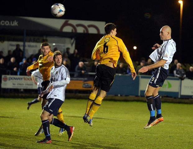 Ilkley Gazette: Guiseley's Danny Ellis powers in their equaliser from Wayne Brooksby's corner