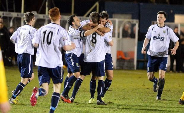 Team-mates help Kevin Holsgrove celebrate after his goal helped defeat Leamington on Tuesday night