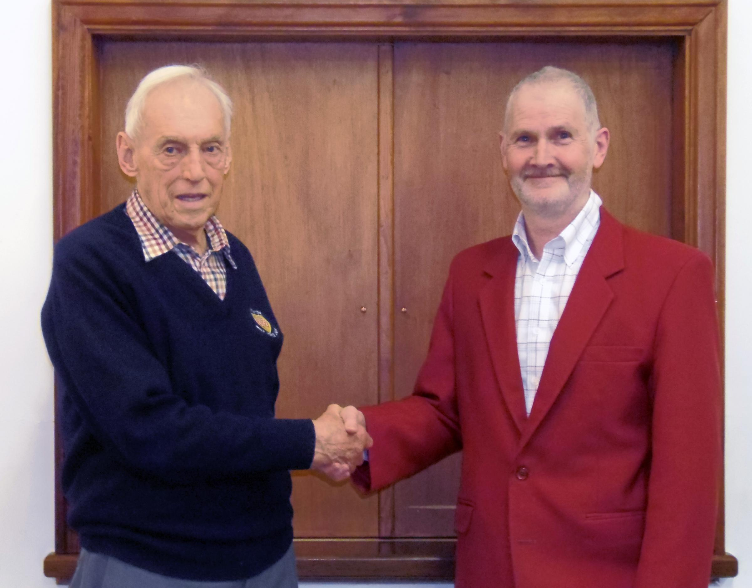 Paul Duff, right, receives his red choir jacket from Ken Wardell