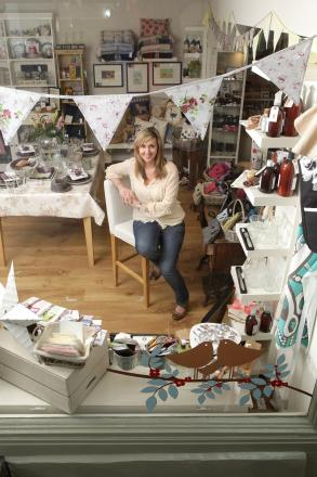 Nora's owner Victoria Newhouse framed within her shop window which has been shortlisted for a Best Retail Display award