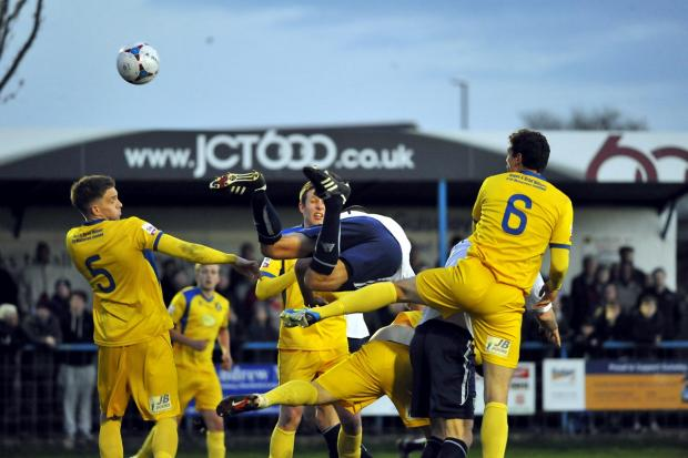 Ilkley Gazette: Guiseley's Danny Hall goes flying as he tanngles with the Gainsborough Trinity defence