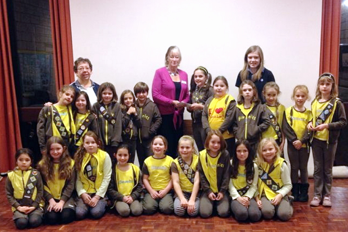 Lucy Otway (presenting the cheque) and other members of the 2nd Rawdon Trinity Brownies, who raised money for Martin House