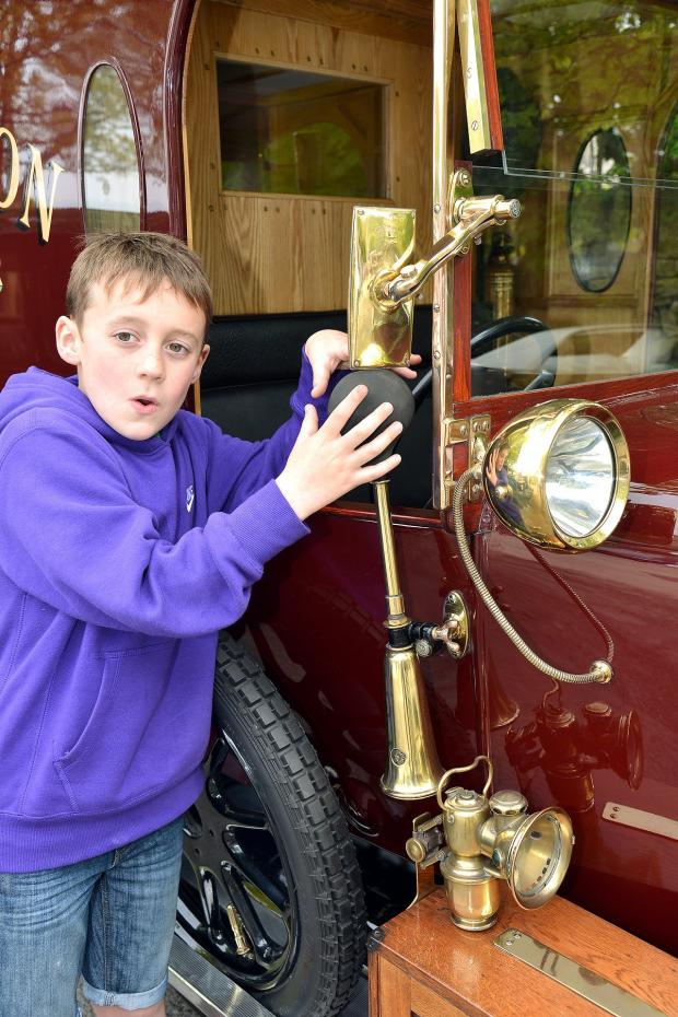 Ilkley Gazette: Alex Ryan, nine, from Otley, tries the horn on one of the vintage cars