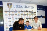 Sami Pattinson signing for the Leeds United Academy under-nine squad with United players Lewis Walters (left) and Eric Grimes