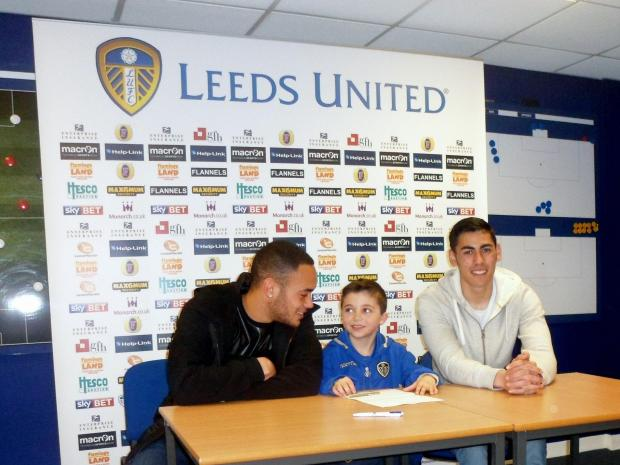 Ilkley Gazette: Sami Pattinson signing for the Leeds United Academy under-nine squad with United players Lewis Walters (left) and Eric Grimes