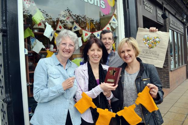 Suzanne Johns, right, presents the winning shop-window competition trophy to the Duttons for Buttons team, from the left, Sandra Russell, Julie Mullins and Baldrick West
