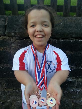 Savannah Troughton-Webb proudly displaying her medals