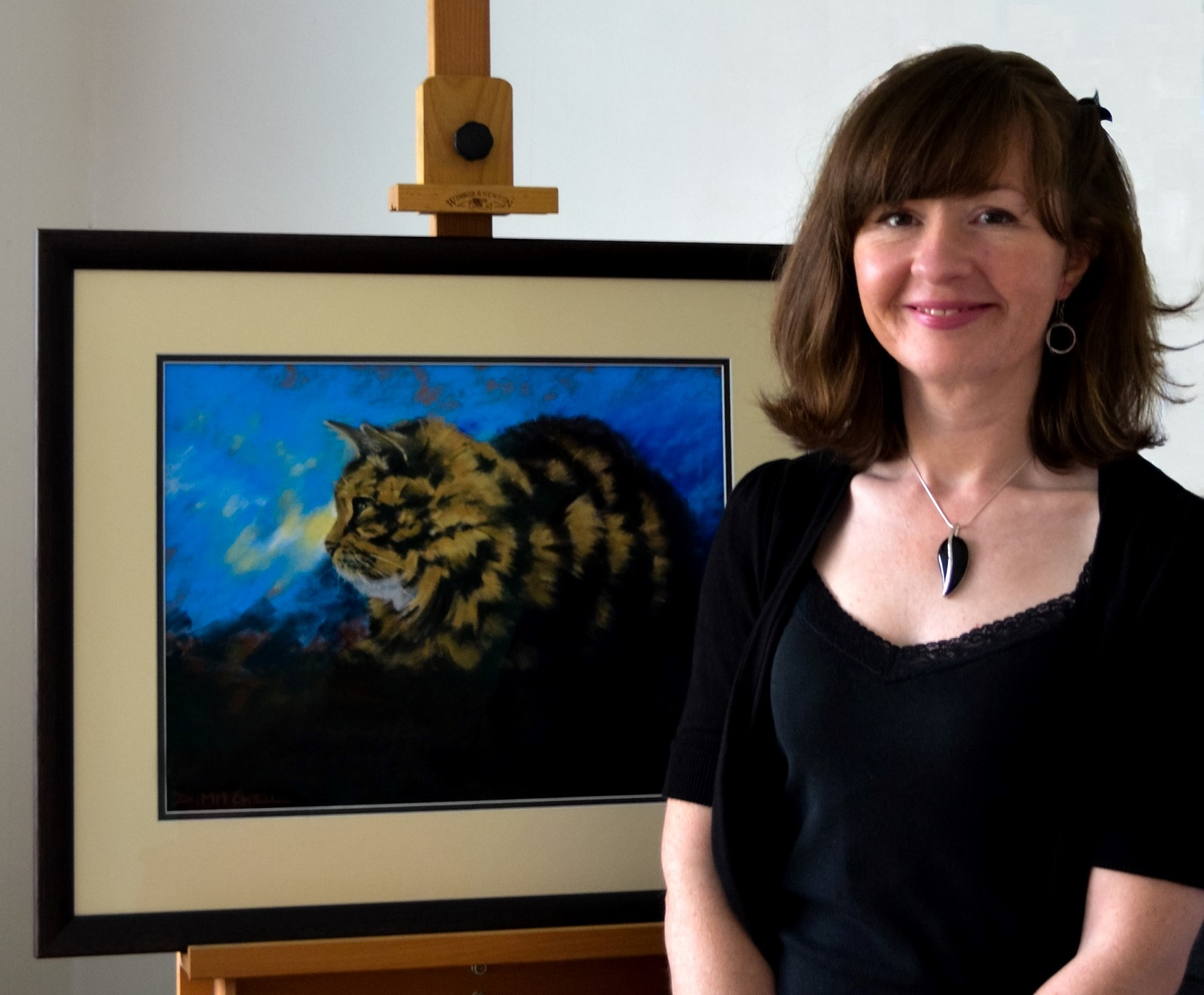 Artist Denise Mitchell with one of her paintings