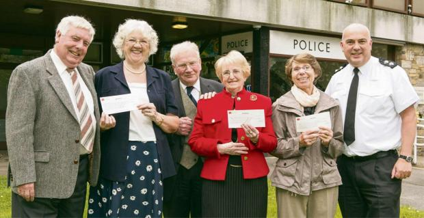 Ilkley Gazette: submitted pix: Caption: Proceeds from the most recent open day at Otley Police Station will help three local charities. L-R: Dave Robson and Hazel Lee of Otley & District Road Safety Committee, Keith and Beryl Harland of Horsforth Retired People's