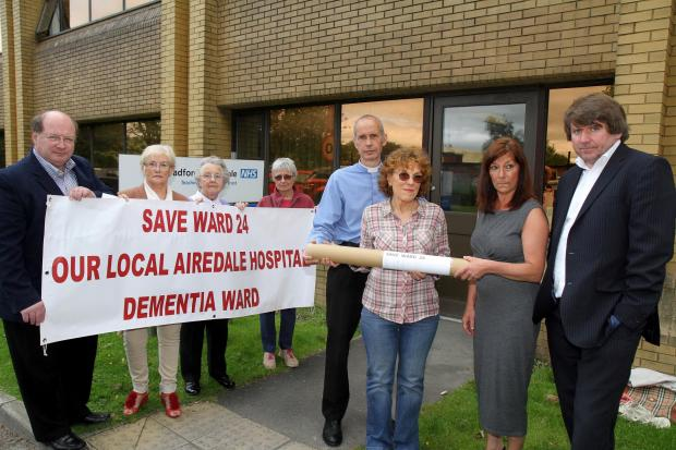 Ilkley Gazette: Silsden priest and Airedale Hospital chaplain the Rev David Griffiths, centre, joins campaigners handing a petition over the ward 24 closure to members of the Airedale, Wharfedale and Craven Clinical Commissioning Group, right.