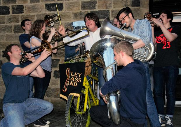 Otley Brass Band's musical director Will Rowson wielding a specially crafted, Tour de France inspired, yellow baton with members of the band.