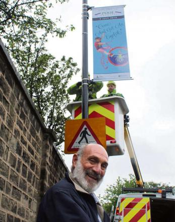 Pool-in-Wharfedale Parish Councillor Richard Parker watches one of the village's Welcome to Pool Tour de France banners go up.