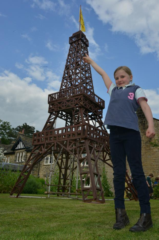 Ilkley Gazette: ZUT ALORS!  Charlotte Collinson (7) pretends to touch the top of the Eifel Tower replica what has been constructed in Burley in Wharfdale. (7742760)