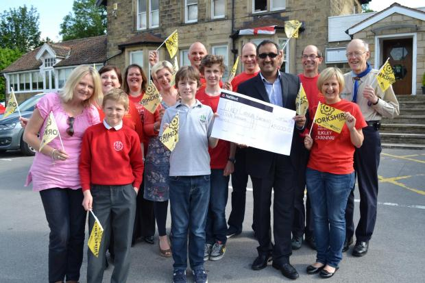 Ilkley Gazette: Beneficiaries, including Debbie and Ben Harris, Vicki, Oscar and Barney Street from LS29 and Robin Beaumont from Ben Rhydding De Mohicanen Scout and Guide Group, join Ilkley Carnival headline sponsor Tariq Mahmood of Kashmiri Aroma and members of the Ilkl