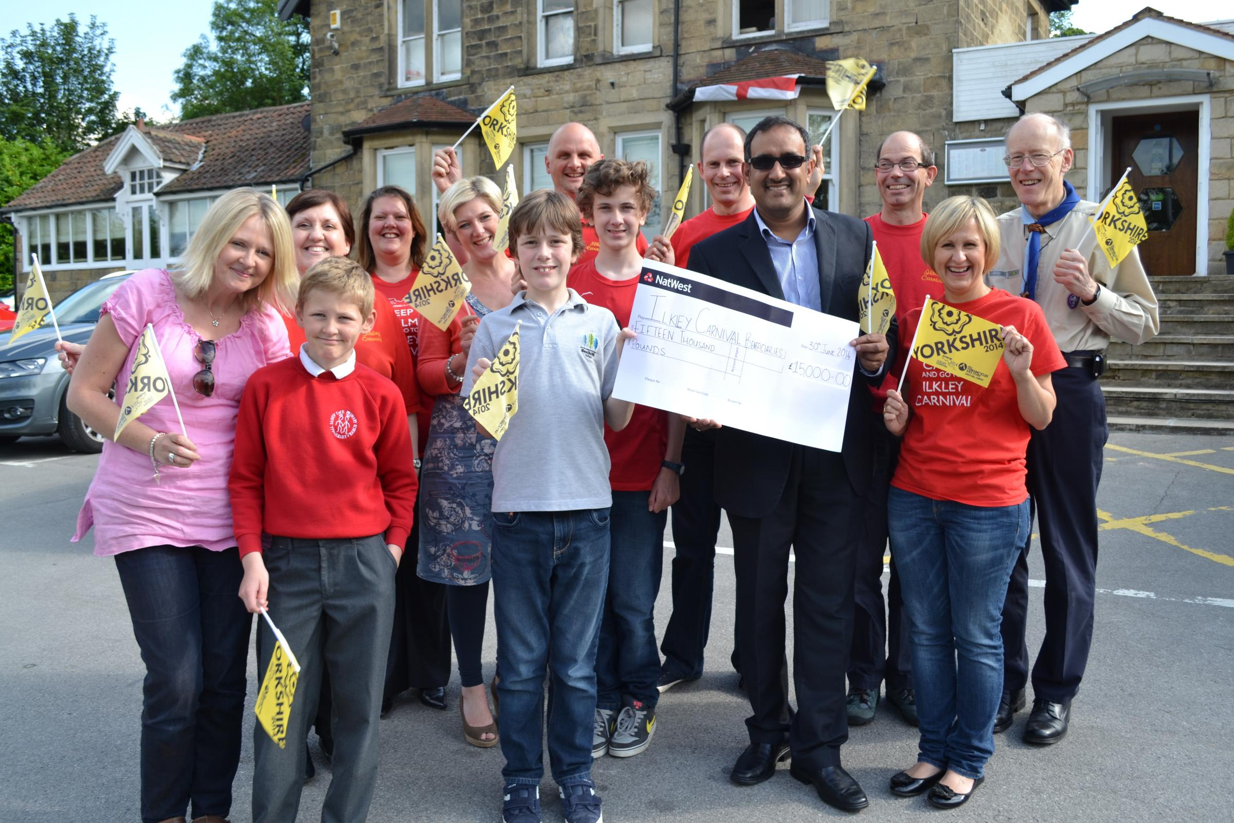 Beneficiaries, including Debbie and Ben Harris, Vicki, Oscar and Barney Street from LS29 and Robin Beaumont from Ben Rhydding De Mohicanen Scout and Guide Group, join Ilkley Carnival headline sponsor
